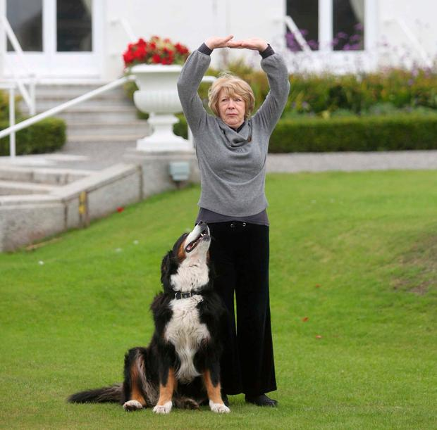Pet: Sabina Higgins stretches on the Áras lawn with Sioda while participating in a Tai Chi reception. Photo: Sam Boal/Rollingnews.ie