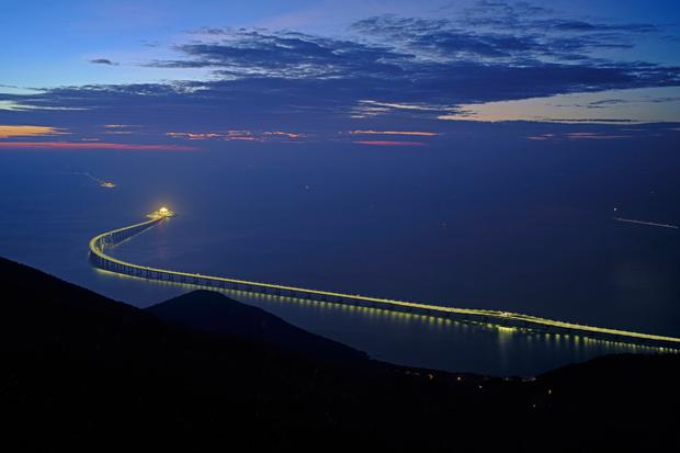 In this Sunday, Oct. 21, 2018, photo, the Hong Kong-Zhuhai-Macau Bridge is lit up in Hong Kong. The bridge, the world's longest cross-sea project, which has a total length of 55 kilometers (34 miles), will have opening ceremony in Zhuhai on Oct. 23. (AP Photo/Vincent Yu)