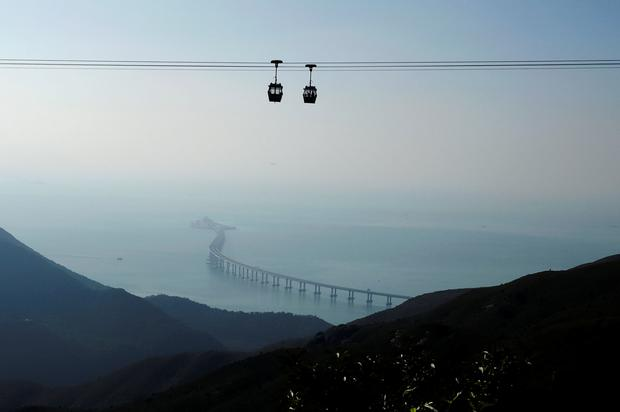 Cable cars move in front of the Hong Kong-Zhuhai-Macau bridge off Lantau island in Hong Kong, China October 21, 2018, before its opening ceremony on October 23, 2018. Picture taken October 21, 2018. REUTERS/Bobby Yip