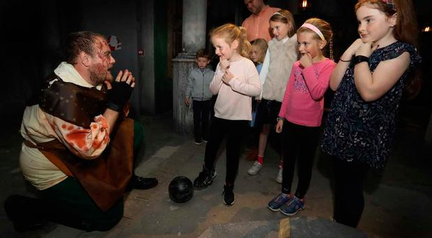 Torturer Jordan Begley scares his audience at Vaults Live (front, r-l) Niamh McGeachan (9), Ciara Winterbotham (7), Hannah McGeachan (6), (back r-l) Helen Winterbotham (9), Freya O'Connor (6), Dave O'Connor and Joey O'Connor (4)