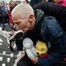 Tears: A woman kisses a baby's shoe during a vigil at the Tuam Mother and Baby Home site to coincide with the papal visit in August. Photo: Ray Ryan