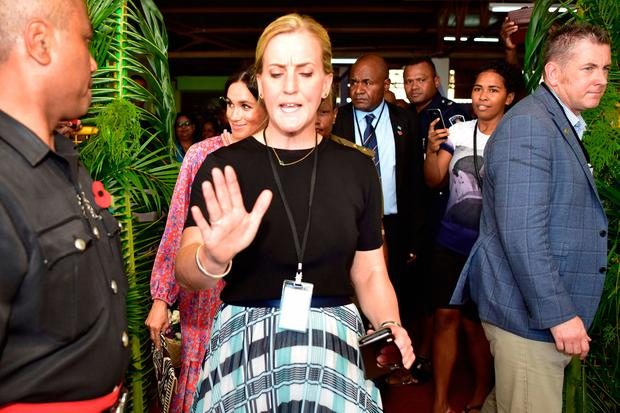 This handout from the Fijian Government taken and released on October 24, 2018 shows Britain's Meghan, Duchess of Sussex (2nd L) leaving the municipal market in Suva