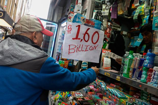 A man buys tickets for Tuesday's Mega Millions lottery drawing after the jackpot exceeded $1.6 billion in New York City, New York