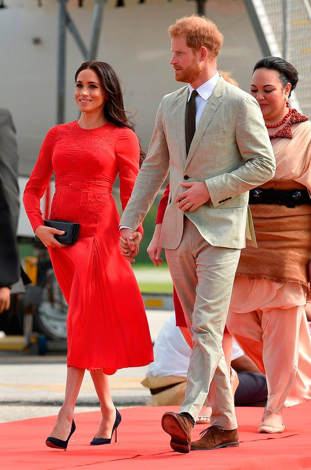 Britain's Prince Harry and his wife Meghan, Duchess of Sussex arrive at Fua'amotu airport in Tonga on October 25, 2018