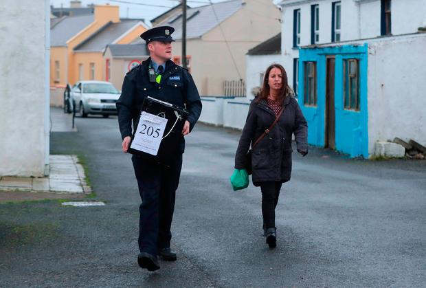 Marian Roarty presiding officer and Garda Eamonn McGinley after arriving by helicopter on Tory Island, off the coast of County Donegal, with a ballot box for the Irish presidential election and referendum on blasphemy. Niall Carson/PA Wire