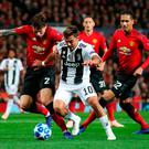Manchester United's Victor Lindelof (left) and Juventus' Paulo Dybala battle for the ball