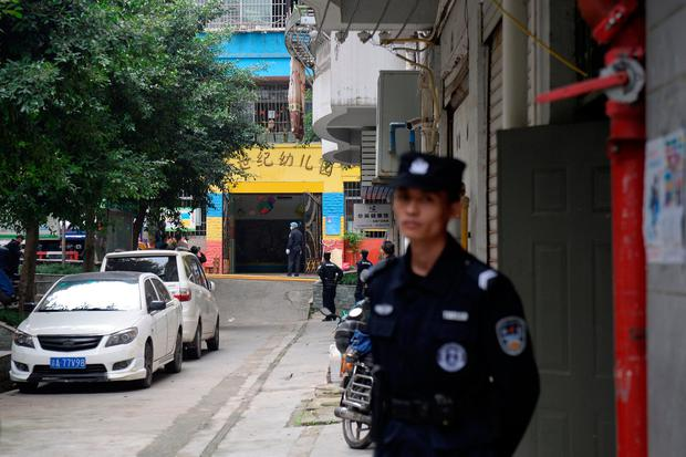 Police officers are seen outside the gate of a kindergarten where a woman armed with a kitchen knife attacked children in Chongqing, China. Photo: Reuters