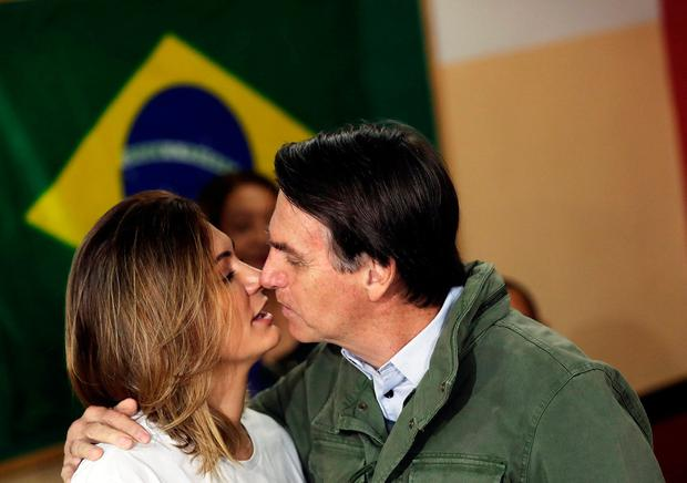 Loving: Far-right candidate Jair Bolsonaro kisses wife Michelle before casting their votes in Rio de Janeiro. Photo: Reuters