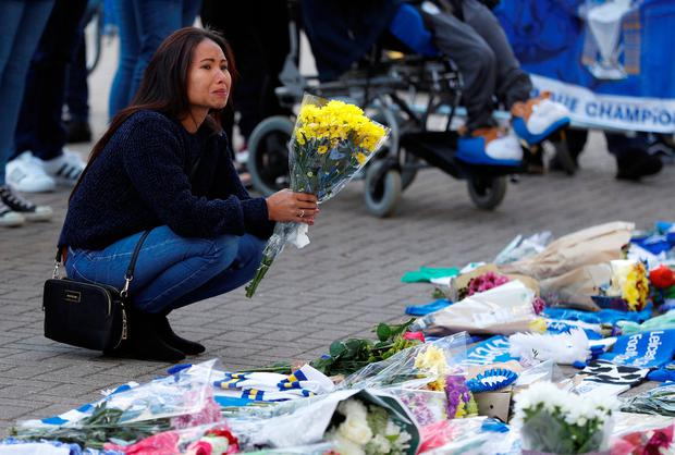 Memorial: A woman is in tears as she leaves flowers outside the stadium. Photo: REUTERS/Peter Nicholls