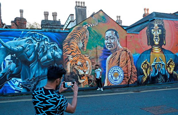 REFILE - CORRECTING ID Visitors take photos in front of a mural representing Buddhist monk Phra Prommangkalachan, after the helicopter of the Leicester City owner Vichai Srivaddhanaprabha crashed when leaving the ground on Saturday evening after their match, in the centre of Leicester, Britain, October 28, 2018. REUTERS/Peter Nicholls