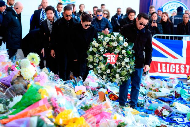 Aiyawatt Srivaddhanaprabha (front) and family members walk through tributes to lay a wreath in memory of Vichai Srivaddhanaprabha, who was among those to have tragically lost their lives on Saturday evening when a helicopter carrying him and four other people crashed outside King Power Stadium. PRESS ASSOCIATION Photo. Picture date: Monday October 29, 2018. Broken-hearted Leicester have paid tribute to