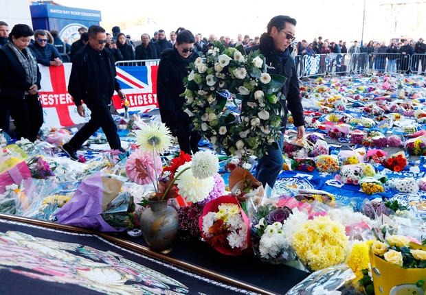 Khun Aiyawatt Srivaddhanaprabha, and Aimon Srivaddhanaprabha, son and wife of Leicester City's owner Thai businessman Vichai Srivaddhanaprabha, lay a wreath for Vichai and four other people who died when the helicopter they were travelling in crashed as it left the ground after the match on Saturday, in Leicester, Britain, October 29, 2018. REUTERS/Peter Nicholls