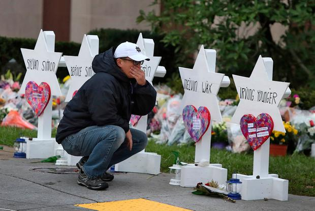 Public grief: Tears are shed yesterday at a makeshift memorial to the victims of the massacre outside the Tree of Life synagogue in Pittsburgh. Photo: Reuters