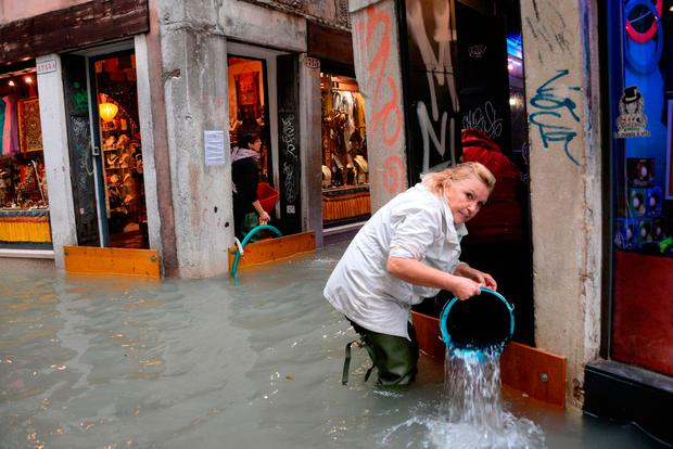 A woman removes water from a shop in Venice. Photo: AP