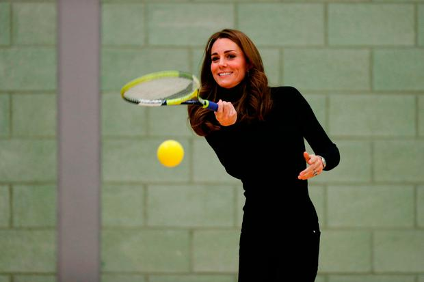Britain's Catherine, Duchess of Cambridge, plays tennis as she joins a session with a group during a visit the Coach Core Essex apprenticeship scheme at Basildon Sporting Village in Basildon, southeast England, on October 30, 2018