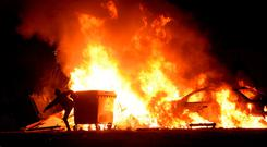 General view of boy attempting to kick wheeled bin into the bonfire alongside a burning car on Halloween evening. Finglas south, Dublin. Picture: Caroline Quinn