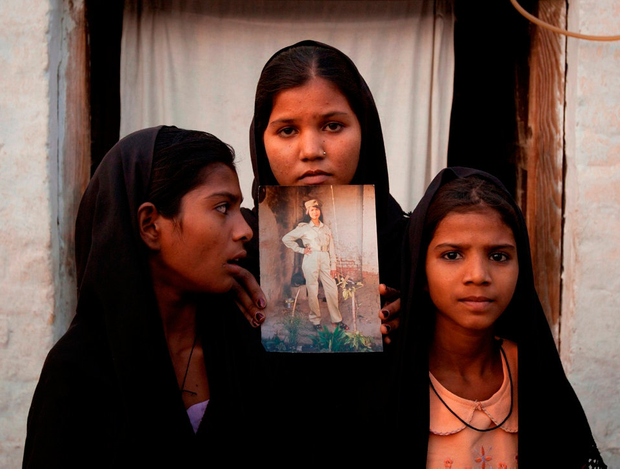 The daughters of Pakistani Christian woman Asia Bibi pose with an image of their mother while standing outside their residence in Pakistan's Punjab Province. Photo: Reuters
