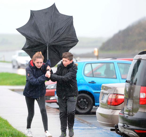 Breezy: Molly and Matthew Navin struggle with their umbrella in Westport, Co Mayo. Photo: Paul Mealey
