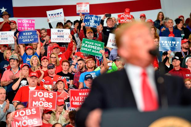 Supporters hold up signs as Donald Trump speaks during a campaign rally at Southport High School in Indiana. Photo: Nicholas Kamm