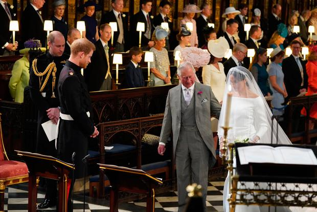Prince Harry looks at his bride, Meghan Markle, as she arrives accompanied by Prince Charles, Prince of Wales during their wedding in St George's Chapel at Windsor Castle on May 19, 2018 in Windsor, England. (Photo by Jonathan Brady - WPA Pool/Getty Images)