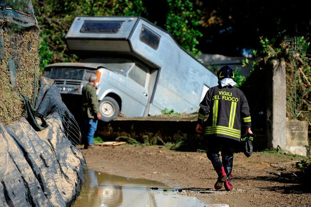 Damage: A fireman walks towards a motorhome in a ditch near the house where two families drowned in Casteldaccia, near Palermo. Photo: Guglielmo Mangiapane/Reuters