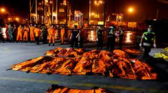 Officials in Jakarta supervise the body bags of passengers recovered from the Lion Air flight. Photo: Beawiharta/Reuters