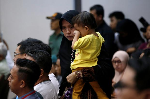 A woman, who had family on the crashed Lion Air flight JT610, walks as she holds her son during a news conference about the recovery process at a hotel in Jakarta, Indonesia, November 5, 2018. REUTERS/Willy Kurniawan