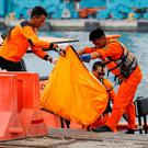 Tragedy: Rescue team members carry a bag containing a body. Photo: Reuters