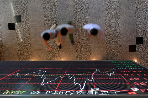People walk under an electronic board showing stock information at the Shanghai Stock Exchange in Lujiazui Financial Area in Shanghai, China. Photo: Reuters