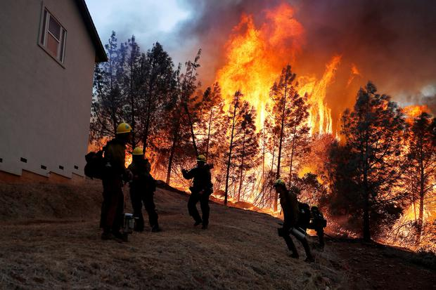 A group of U.S. Forest Service firefighters monitor a back fire while battling to save homes at the Camp Fire in Paradise, California, U.S. November 8, 2018. REUTERS/Stephen Lam