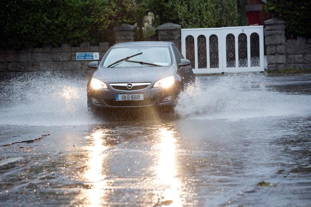 Cars drive through floods at the junction of Bushy Park Road and Zion Road Rathgar. Photo: Tony Gavin 9/11/2018