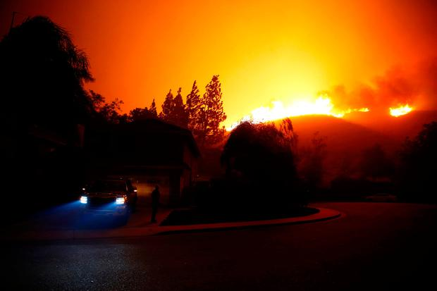 A resident looks at approaching flames as firefighters battle flames overnight during a wildfire that burned dozens of homes in Thousand Oaks, California, U.S. November 9, 2018. REUTERS/Eric Thayer