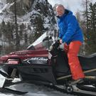 "Communications expert Alan Shortt, who is also well known as a comedian, poses on a Cortina snowmobile, ""downhill slopes can be an adrenaline rush"""