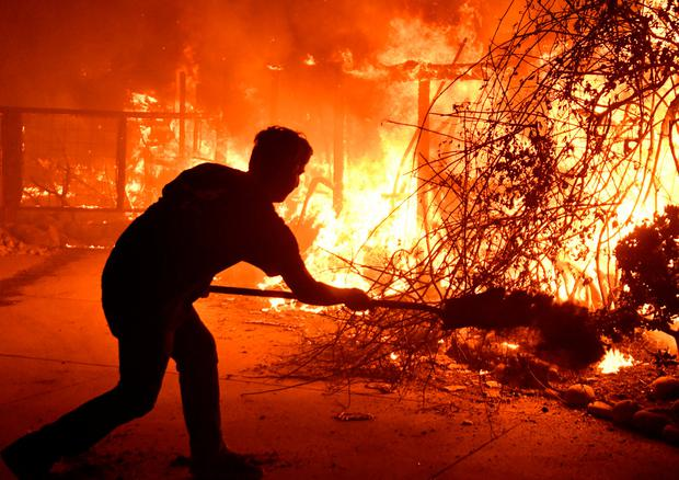 A man uses a shovel with dirt to try to stop the flames approaching. Picture: Reuters