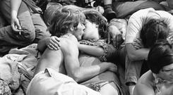 ERA OF LOVE: A couple kiss in the crowd at a music festival in 1970 — a time of sexual revolution. Picture: William Lovelace/Getty