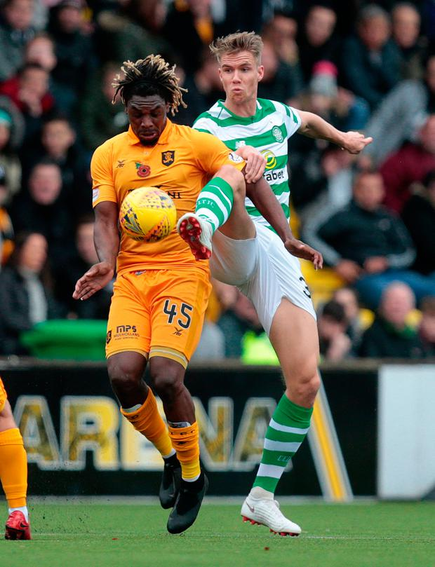 Livingston's Dolly Menga (L) vies with Celtic's Kristoffer Ajer (R)