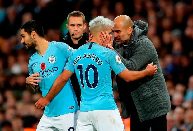 Manchester City manager Pep Guardiola (right) speaks to Sergio Aguero (centre) as he is substituted for Ilkay Gundogan (left)