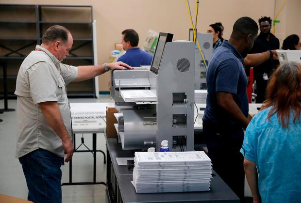 An official loads a machine to automatically count votes in Broward County, Florida. Photo: Joe Skipper/Getty Images