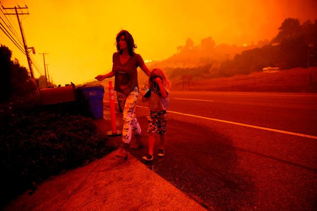 A woman and her child prepare for evacuation in Malibu. Photo: Eric Thayer/Reuters