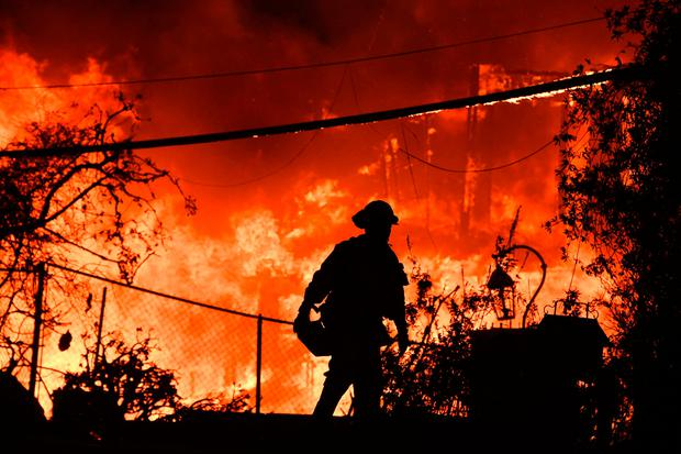 Blaze: A firefighter is silhouetted by a burning home along Pacific Coast Highway (Highway 1) during the Woolsey Fire in Malibu. Photo: Robyn Beck/Getty images