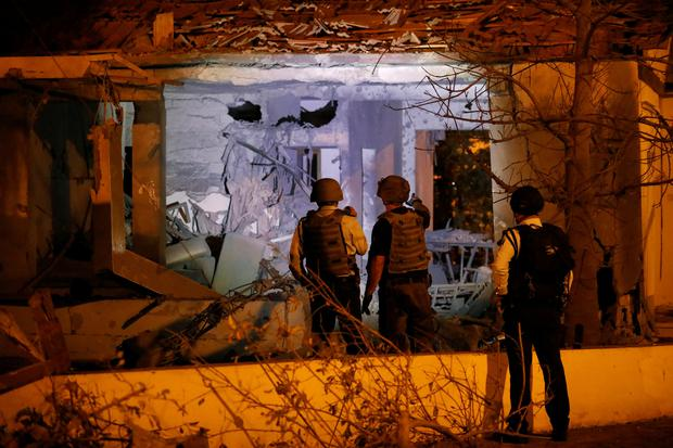 Security personnel check a damaged house in the Israeli city of Ashkelon, following a rocket attack from Gaza November 12, 2018. REUTERS/ Amir Cohen
