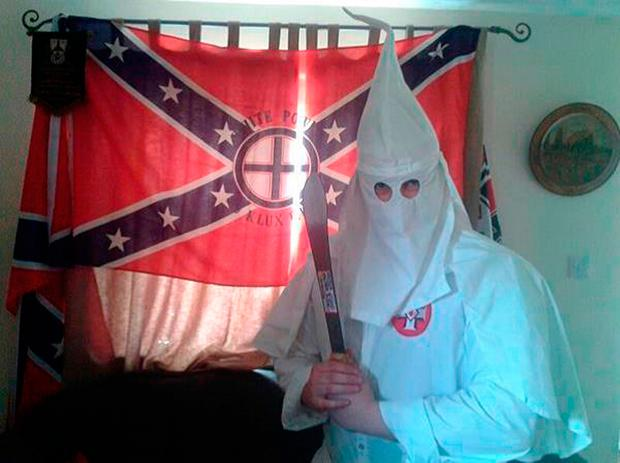 Undated handout file photo issued by West Midlands Police of a picture allegedly showing Adam Thomas wearing the hooded white robes of the Ku Klux Klan (KKK) whilst brandishing a machete in front of a KKK flag at his home in Oxfordshire. West Midlands Police/PA Wire