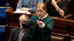 Action: Ruth Coppinger holds up a thong in the Dáil chamber as she urges Government to stop 'rape myths' being used in court