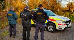 Raid: CAB officers and gardaí at the scene of the search in Co Meath