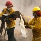 Aftermath: Firefighters comb a house destroyed by fire in Paradise, California. Photo: Reuters