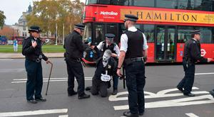 A protestor who was blocking the road is removed by police outside the Houses of Parliament. Photo: Nick Ansell/PA