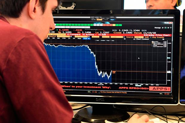 Tumble: A journalist looks at a computer showing the plummet in the value of the pound after the day of chaos. Picture: AFP/Getty