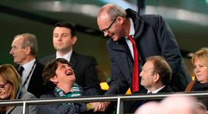 Handshake: Arlene Foster greets Simon Coveney at the Ireland-Northern Ireland friendly. Picture: PA