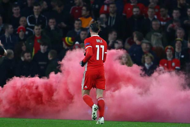 Wales' striker Gareth Bale runs toward a smoke bomb thrown onto the pitch during the UEFA Nations League Group B football match between Wales and Denmark at Cardiff City Stadium in Cardiff on November 16, 2018. (Photo by Geoff CADDICK / AFP)