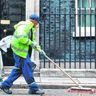 What a mess: A worker sweeps the street outside 10 Downing Street in London yesterday. Photo: Getty Images